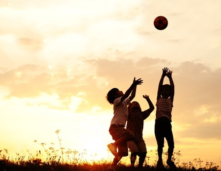 10873865 - silhouette, group of happy children playing on meadow, sunset, summertime
